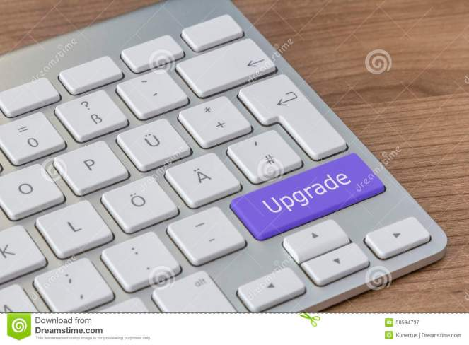upgrade-modern-keyboard-written-large-blue-button-wooden-desktop-50594737
